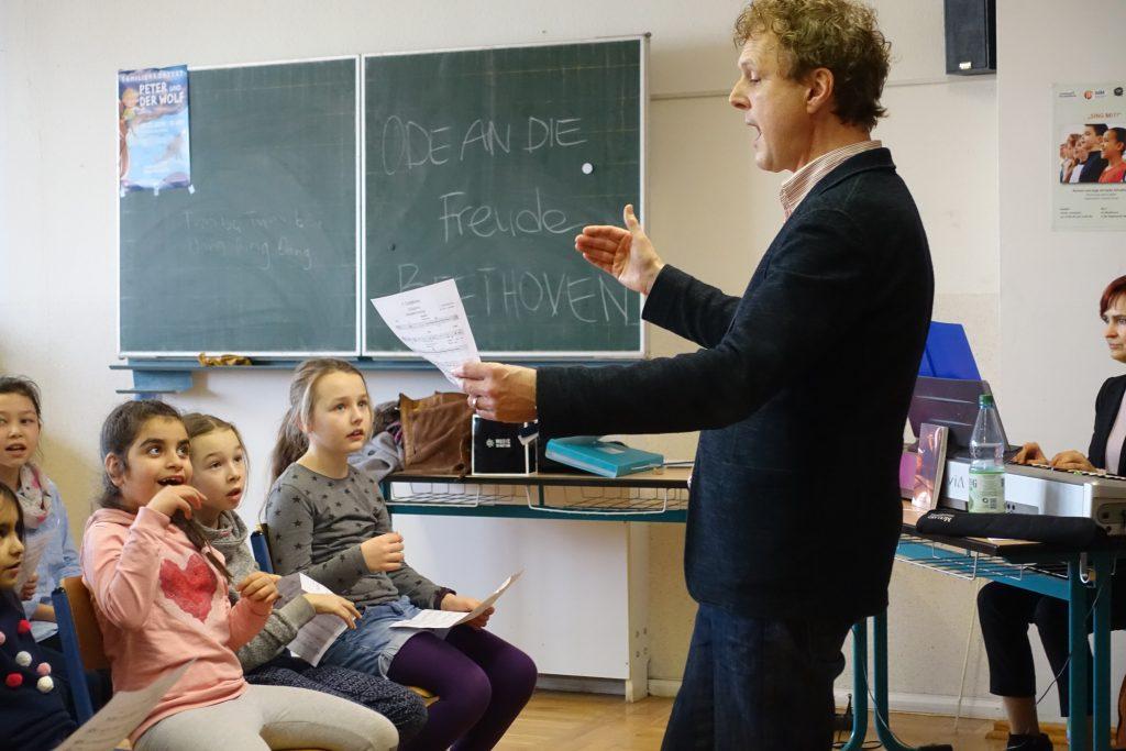 Dirigent Rainer HErsch steht vor den Kindern und singt mit ihnen.
