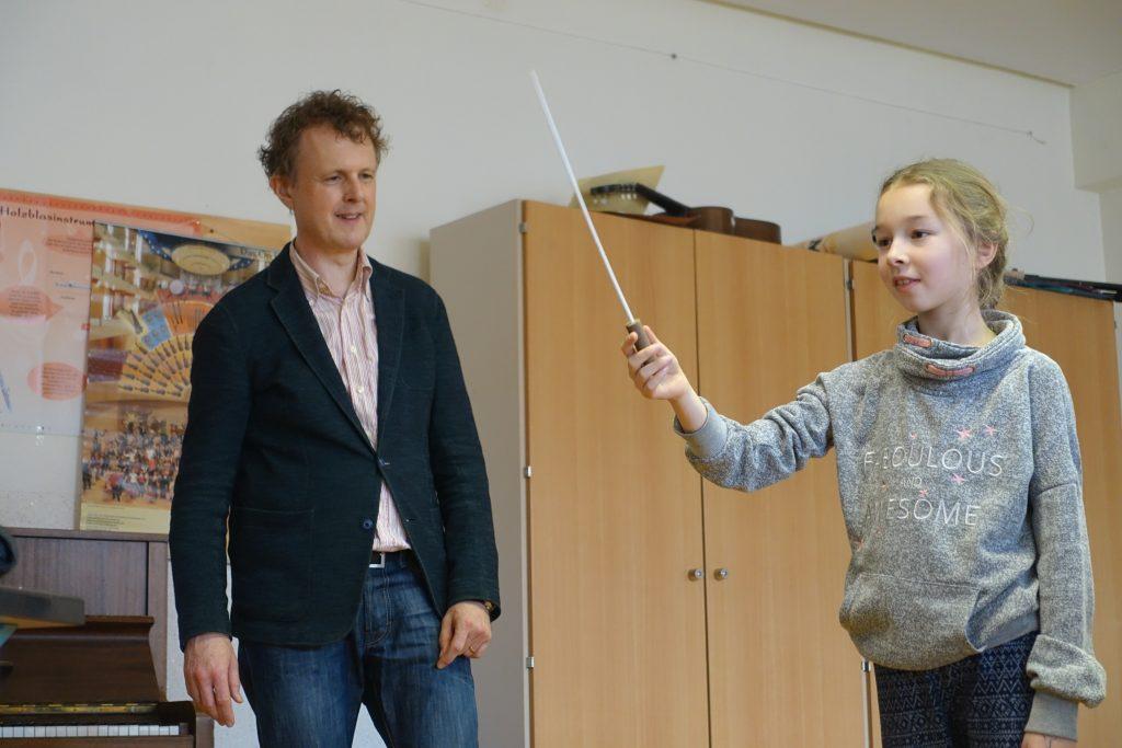 Ein Mädchen steht mit dem Dirgierstab vor der Pianistin am Keyboard und gibt den Takt an. Hinter ihr steht der Dirigent Rainer Hersch.