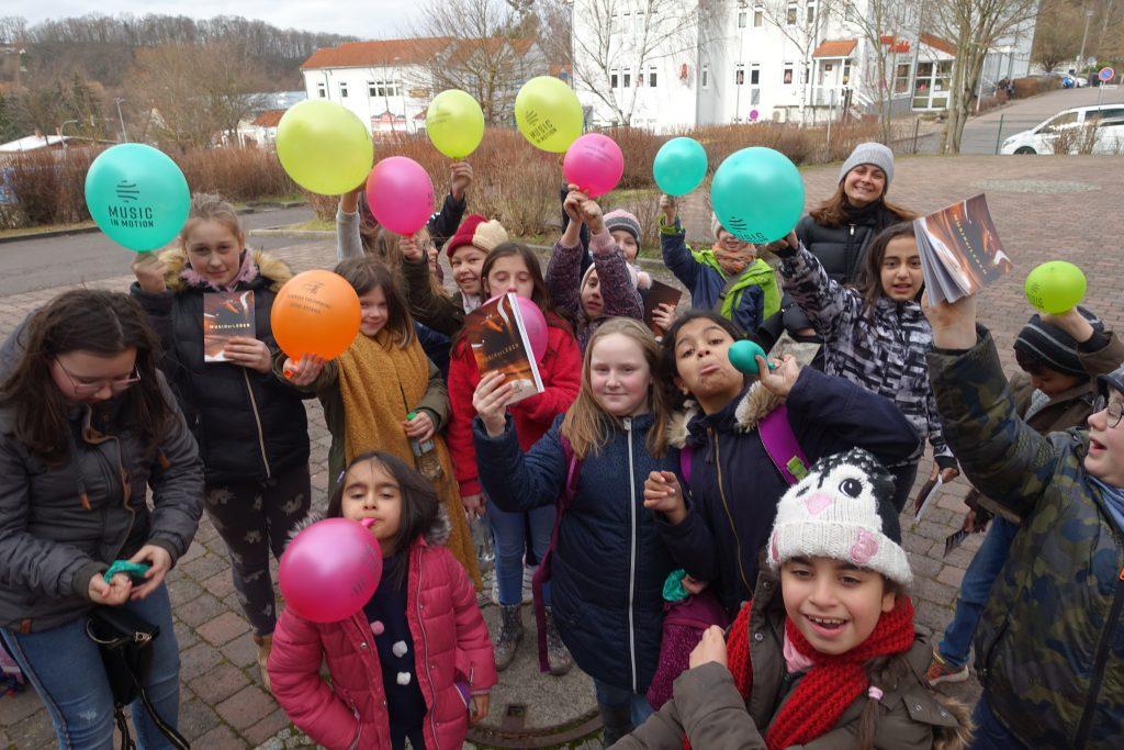 Die Gruppe der Chorkinder aus Eisenach lächelt zur Kamera um die Wette. Viele tragen bunte Luftballons in der Hand.